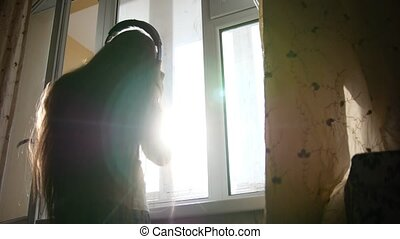 Silhouette of teenager girl in headphones listening to music and dancing in front of the window