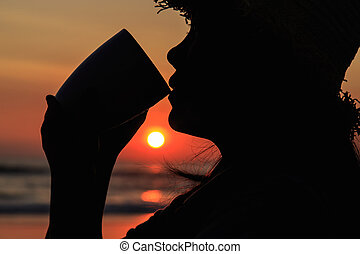 Silhouette of Thai woman drinking holding coffee cup at the beac