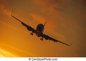 Silhouette of the big plane on a sunset background.