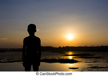 Silhouette of the boy stand watching the sunset on the river.