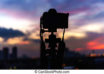 Silhouette of the camera is taking a photo of the twilight at the city