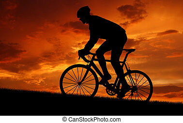bike at sunset - silhouette of the cyclist riding a road...