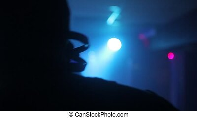 silhouette of the DJ on the background of a striptease dancer in ultraviolet light at a nightclub