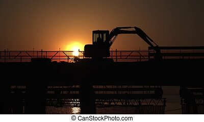 Silhouette at sunset of a construction site on the road with cars and motorbikes passing by