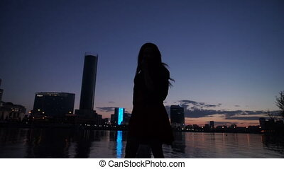 Silhouette of the girl at night on the river bank