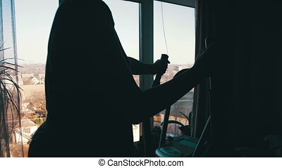 Silhouette of the Girl Exercising on the Cardio Trainer Cross Trainer at Home on Against the Window.