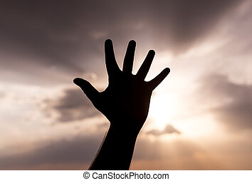 silhouette of the hand on the sunset background