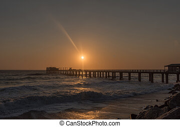 Silhouette of the historic jetty against setting sun in Swakopmund