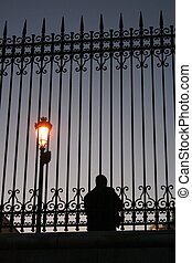 Silhouette of the man against a fence