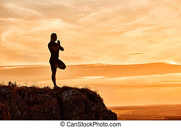 Silhouette of the man practicing yoga on the hill against beautiful sunset.