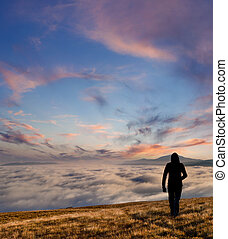 silhouette of the man walking above the clouds on the ...