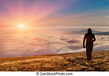 silhouette of the man walking above the clouds on the sunrise