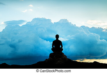 Silhouette of the meditating person against an approaching...
