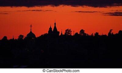 Silhouette of the monastery against beautiful orange sunset...