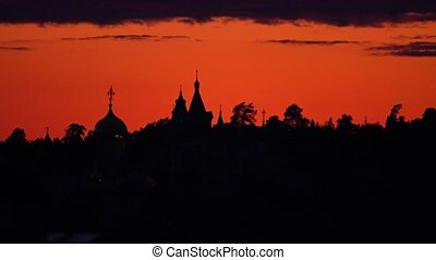 Silhouette of the monastery against beautiful orange sunset sky