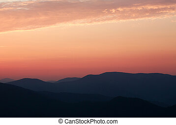 Silhouette of the mountain hills against setting sun and colorful sunset sky