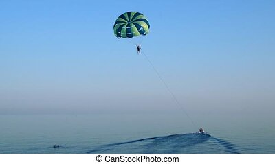 Towing a parachute behind a boat over the sea at sunset....