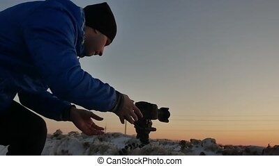 silhouette of the photographer at sunset. man photographer...