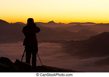Silhouette of the photographer over a foggy mountain