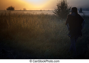 Silhouette of the phototraveler against fog landscape over a flower meadow, the first rays of dawn and dark silhouettes of trees against a sunrise, selective focus