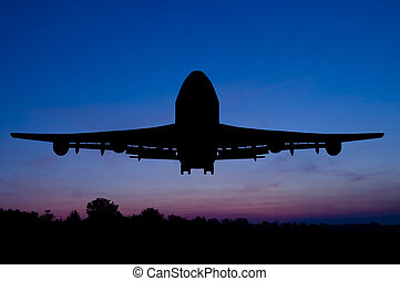 Silhouette of the plane starting on a sunset background.