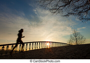 Silhouette of the running girl at sunrise on the bridge