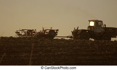 silhouette of the sunset farmer in tractor Russia...