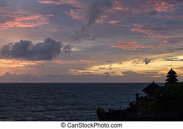 Silhouette of the temple of Tanah Lot on the background of purple sunset