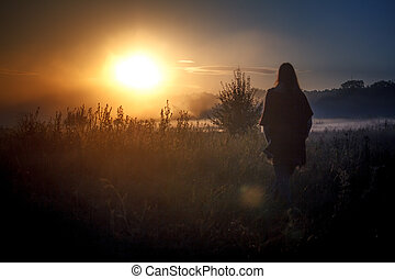 Silhouette of the traveler against fog landscape over a flower meadow, the first rays of dawn and dark silhouettes of trees against a sunrise, selective focus