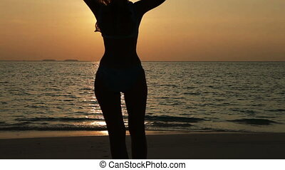 Silhouette of the woman against a sunset at ocean,