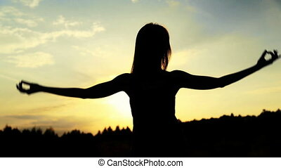 Silhouette of the woman dancing during beautiful sunset. Natural light and darkness.