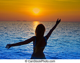 Silhouette of the woman giving hands to a sunset in the sea