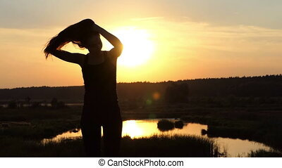 Silhouette of the young girl play with her hairsr at sunset in slow motion.