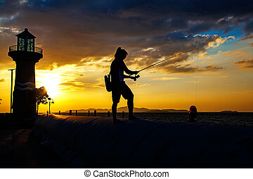 Silhouette of the young man fishing near the beach., with beautiful lighthouse and sunset behind.