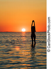 Silhouette of the young woman with hands upwards on a bay on a sunset