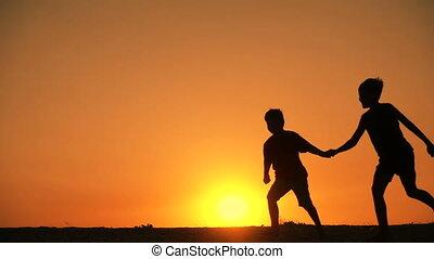 silhouette of three boys runniing at sunset