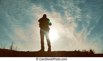 Silhouette of tourist traveler man hiker. Man With Backpack...