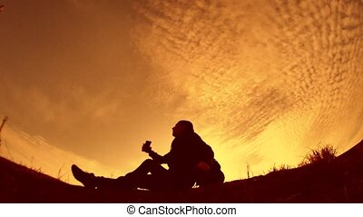 Silhouette of tourist traveler man hiker sits resting with a...