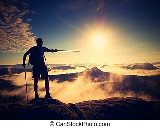 Silhouette of tourist with poles in hand. Sunny spring land
