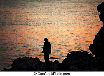Silhouette of trekker on rocky seashore near camping tent on overnight stay
