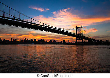 Silhouette of Triborough bridge and city with sunset sky, New York