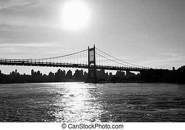 Silhouette of Triborough bridge over reflective river and buildings in black and white style, New York