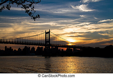 Silhouette of Triborough bridge over the river and city with sunset sky, New York