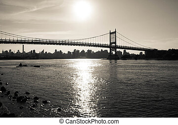 Silhouette of Triborough bridge over the river and the city in dark vintage style, New York