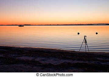 Silhouette of tripod with camera taking picture on beach at sunset