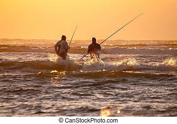 Silhouette of two anglers against sunset