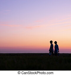 silhouette of two boys against colorful sunset
