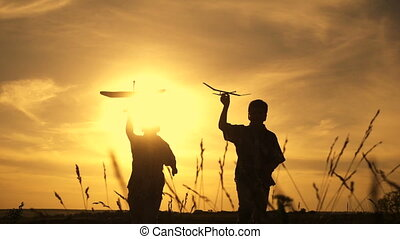 Silhouette of two boys running with airplanes at sunset