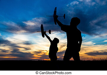 Silhouette of two boys with his airplanes against sunset