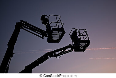 Silhouette of two cherry pickers against the evening sky